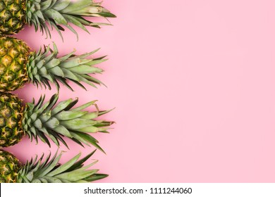 Pineapple fruit side border on a pastel pink background. Top view, flat lay with copy space.
