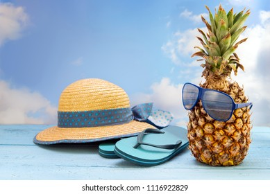 pineapple fruit with sunglasses, flip flop beach sandals and a straw hat against a blue sky with clouds, summer vacation concept with copy space, selected focus, narrow depth of field