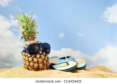 pineapple fruit with sunglasses and flip flop sandals on the beach sand against a blue sky with clouds, summer vacation concept, copy space, selected focus