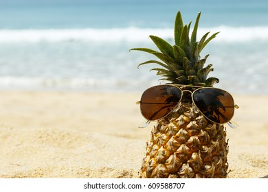 Pineapple fruit and sunglasses on the beach