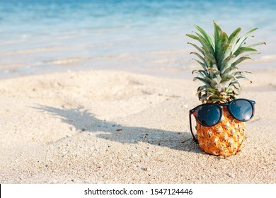 Pineapple fruit in sunglasses on sand against turquoise caribbean sea water. Tropical summer vacation concept