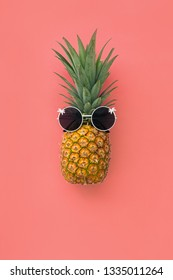 Pineapple funny face in sun glasses on pink pastel background, summer tropical  concept, flat lay