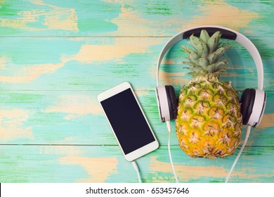 Pineapple with headphones and smart phone on wooden background. Tropical summer vacation and beach party concept. View from above