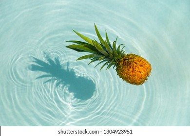 Pineapple into water on sunny beach. Beach and tropical theme. Vacation concept.