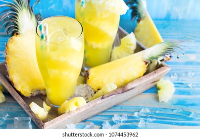 Pineapple juice and fresh ripe pineapple on wooden background