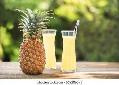 Pineapple juice glass on wooden table with green background