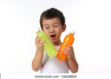 Pineapple juice or Orange juice?/Kid Choosing between pineapple juice and orange juice.