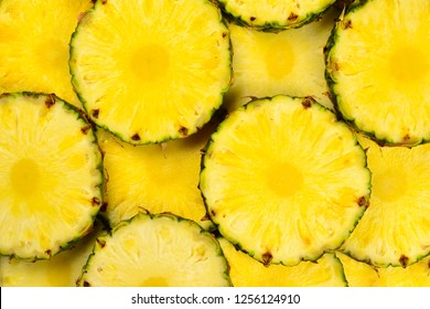 Pineapple juicy yellow slices background. Top view.