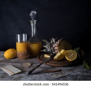 pineapple, lemon, tropical juice, old silver knife on a wooden table