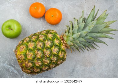 Pineapple, mandarines and apple on the stone
