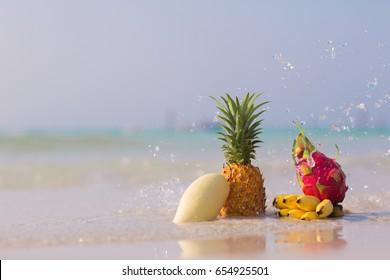 Pineapple, mango, dragon fruit and bananas on the beach