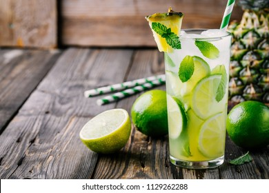 Pineapple Mojito cocktail with lime slices and mint in glass on wooden background