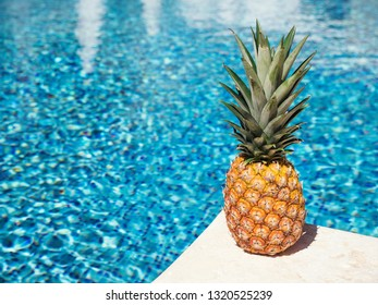 Pineapple near swimming pool at poolside. Creative food and travel concept card