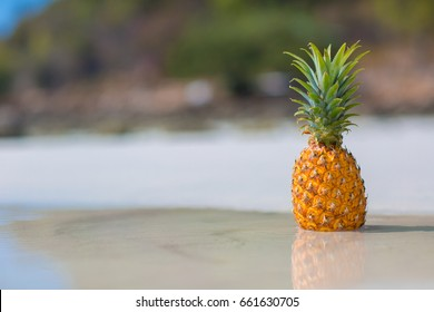 Pineapple on the beach in water on white sand background