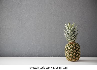 Pineapple on the table against gray wall