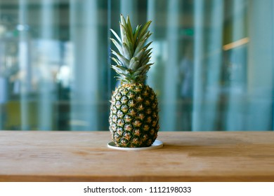 Pineapple on the wooden table. He stands on the background curtain in the office.