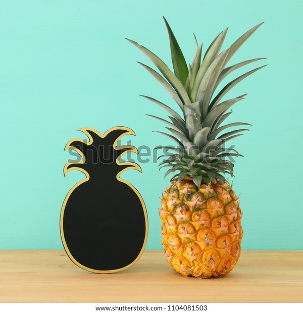 Pineapple on wooden table next to empty blackboard. Beach and tropical theme