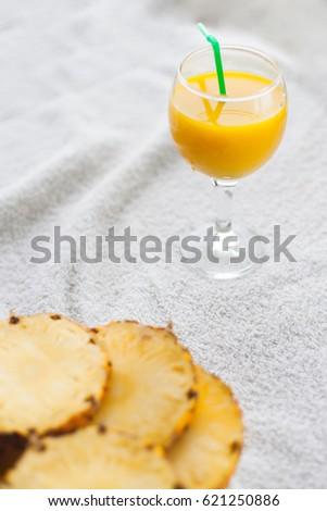 Pineapple, orange juice in a glass with a straw, fresh healthy food, pineapple slices.