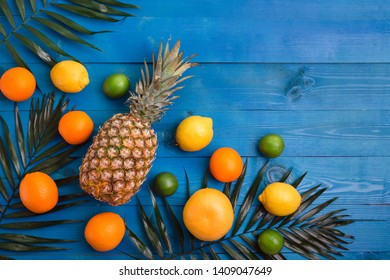 Pineapple, orange, lemon, grapefruit, lime and palm leaves on blue wooden background