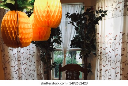 Pineapple paper lanterns in front of a dining room window.