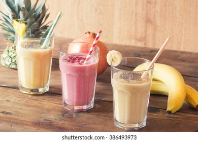 Pineapple, Pomegranate and Banana smoothie with chia seed on wooden table.