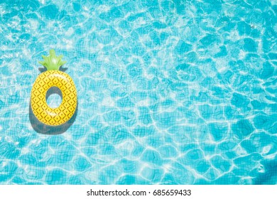 Pineapple pool float, ring floating in a refreshing blue swimming pool