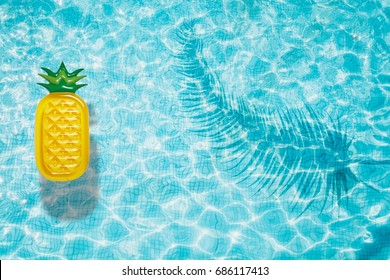 Pineapple pool float, ring floating in a refreshing blue swimming pool with palm tree leaf shadows in water