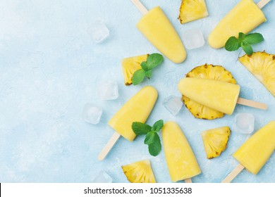 Pineapple popsicles or homemade ice cream top view. Summer refreshing food. Frozen fruit pulp.