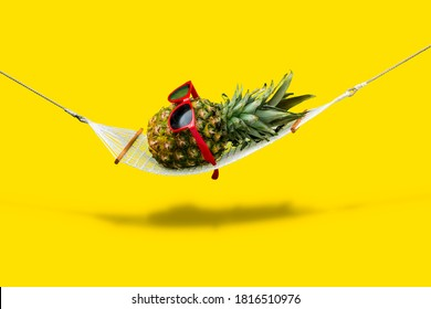 Pineapple with red sunglasses relaxing in hammock on clean yellow background. Vacation or wellness concept.