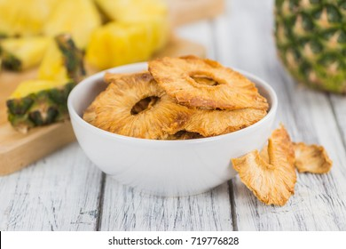 Pineapple rings (dried) on rustic wooden background as close-up shot