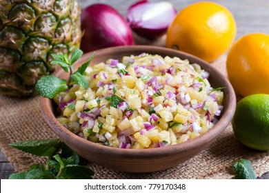 Pineapple salsa with fruit in a bowl on the table