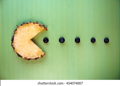 Pineapple slice in the shape of pac-man figure eating blueberries