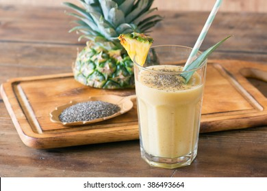 pineapple smoothie with chia seed on wooden table.