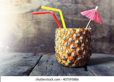pineapple with straw and cocktail umbrella