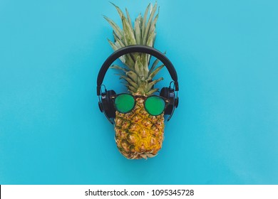 pineapple in stylish hipster sunglasses and black headphones on blue trendy paper background, flat lay. modern summer vacation concept. fruit flat lay, pool party and music theme