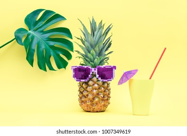 Pineapple with summer cooler cocktail on it's vacation under tropical leaf, cute summer concept, front view