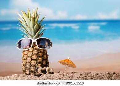 Pineapple with sunglasses near little hearts on the sandy beach