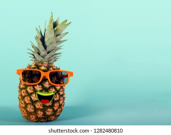 Pineapple in sunglasses - party, fun concept over colorful background