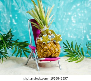 Pineapple in sunglasses  relaxes on  lounge chair on  beach. Summer tropical minimal humor poster.