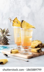 Pineapple Sunrise Mimosas ready for drinking against a light background. - Shutterstock ID 1865889799