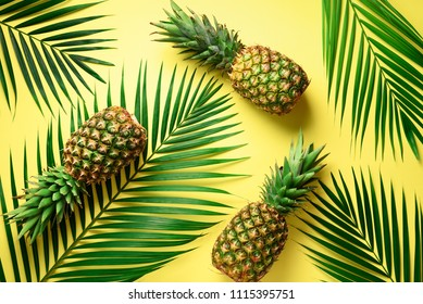 Pineapple and tropical palm leaves on yellow background. Top view. Summer concept. Creative flat lay with copy space