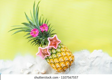 Pineapple wears pink star-shaped glasses on  yellow background Sand and sea shells, pink flowers arranged