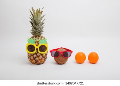 Pineapples and a coconut wearing sunglasses on white background