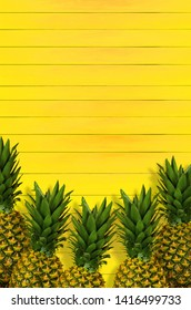 Pineapples on yellow wooden planks
