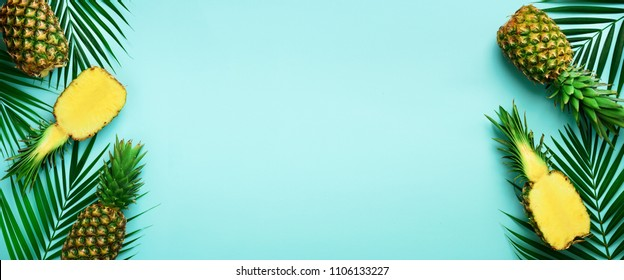 Pineapples and tropical palm leaves on punchy pastel turquoise background. Summer concept. Creative flat lay with copy space. Top view. Banner.