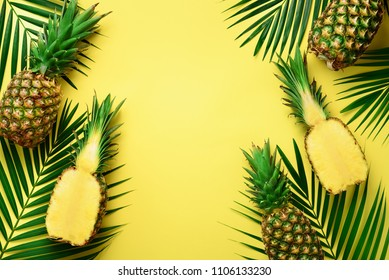 Pineapples and tropical palm leaves on punchy pastel yellow background. Summer concept. Creative flat lay with copy space. Top view.