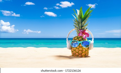 PinePineapple with sunglasses and headphones at tropical beach - Holiday Vacation Concept - Shutterstock ID 1722136126