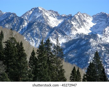 Pines, bare Aspens and snowy peaks in the Colorado Rockies
