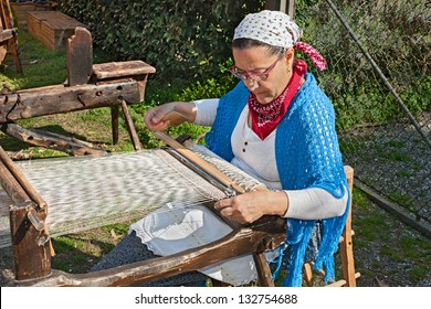 """PINETA DI CLASSE, RAVENNA, ITALY - APRIL 3: unidentified woman weaves with an old loom for recall the old works at """"Green Days"""" festival on April 3, 2011 in Pineta di Classe, Ravenna"""