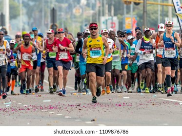 PINETOWN, DURBAN, SOUTH AFRICA - JUNE 10, 2018: Midday many unknownn runners passing through Pinetown whilst competing in the 2018 Comrades marathon between Pietermaritzburg and Durban in South Africa
